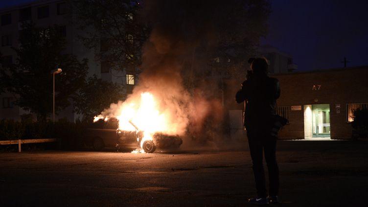 Une voiture incendiée dans la banlieue de Stockholm (Suède),le 21 mai 2013. (JONATHAN NACKSTRAND / AFP)