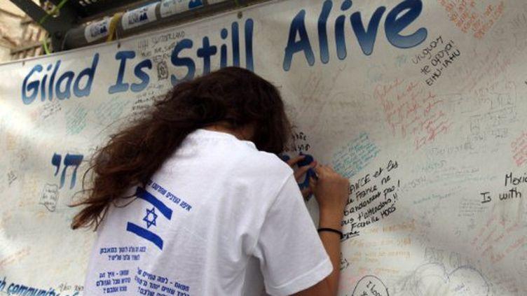 Une jeune Israélienne affiche son soutien au soldat Shalit, à Jérusalem, devant l'habitat de Benjamin Netanyahu. (GALI TIBBON / AFP)