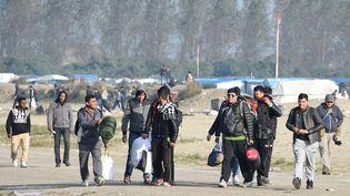"""Des migrants quittent """"la jungle"""" de Calais pendant l'évacuation du camps, le 25 octobre 2016. (DENIS CHARLET / AFP)"""