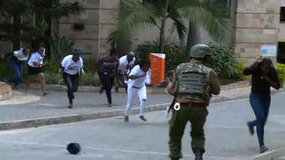 Des personnes courent pour fuir une attaque armée contre un complexe hôtelier, le 15 janvier 2019 à Nairobi (Kenya). (RAPHAEL AMBASU / AFP)