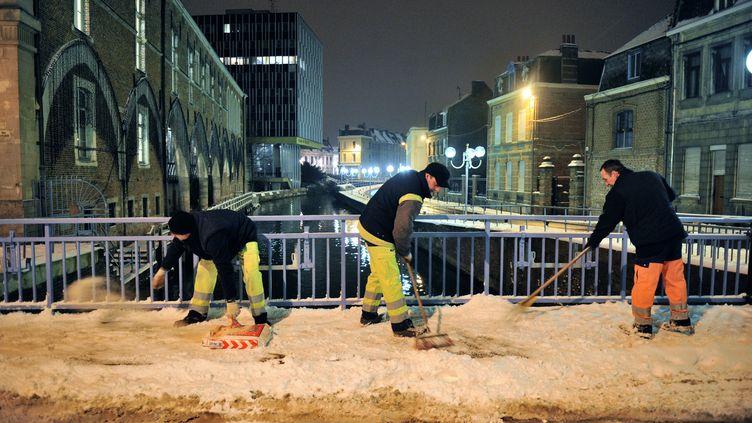 Des employés municipaux dégagent les trottoirs de la neige, le 21 janvier 2013 à Douai dans le nord de la France. (PHILIPPE HUGUEN / AFP)