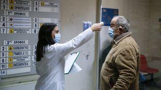 Une soignante grecque face àun patient à Athènes (Grèce), le 20 janvier 2021. (ARIS OIKONOMOU/ SOOC / SOOC VIA AFP)