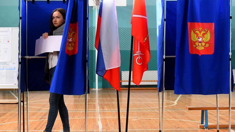 Une femme sort d'un isoloir lors de l'élection du gouverneur de Saint-Pétersbourg (Russie), le 8 septembre 2019. (OLGA MALTSEVA / AFP)