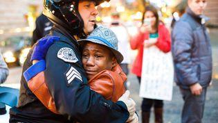 Un jeune garçon de 12 ans enlace un policier pendant une manifestation à Portland (Oregon, Etats-Unis), le 25 novembre 2014. La veille, Darren Wilson, le policier blanc qui avait abattu en août Michael Brown, un jeune Noir désarmé, avait été lavé de tout soupçon par un jury populaire. (JOHNNY NGUYEN / AP / SIPA)