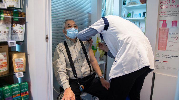 Un pharmacien injecte une dose de vaccin contre le Covid-19 à un patient, à Paris, le 12 mars 2021. (MARTIN BUREAU / AFP)