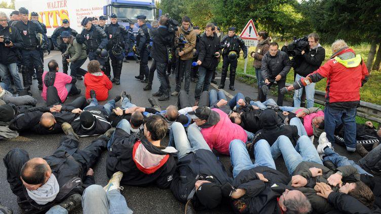 Les salariés de Lampaul-Guimiliau (Finistère) couchés devant les CRS à l'entrée de l'usine de Josselin (Morbihan), le 23 octobre 2013. (FRED TANNEAU / AFP)