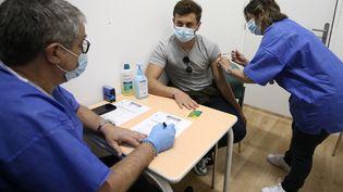 Un homme de 21 ans reçoit une injection du vaccin Pfizer contre le Covid-19, le 13 mai 2021, à Ajaccio (Corse du Sud). (PASCAL POCHARD-CASABIANCA / AFP)