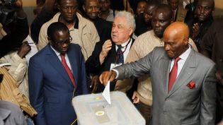 Le président sénégalais, Abdoulaye Wade (à dr.), vote à Dakar (Sénégal), le 26 février 2012. (YOUSSEF BOUDLAL / REUTERS)
