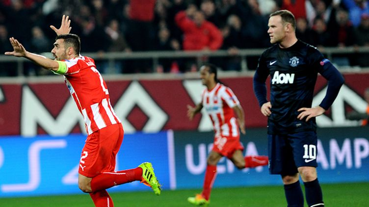 Giannis Maniatis célèbre le but de l'Olympiakos, devant un Wayne Rooney dépité (YANNIS KOLESIDIS / AFP)