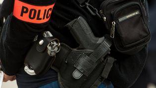 Un brassard police et une arme de policier, le 1 mars 2017. (PHILIPPE HUGUEN / AFP)