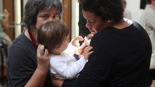 Un couple de femmes homosexuelles tiennent leur enfant, le 17 septembre 2010 à Paris. (CELINE MIHALACHI / AFP)