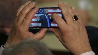 Un homme prend un cliché de Donald Trump, le 6 octobre 2016 à Sandown (Etats-Unis). (MARY SCHWALM / AFP)