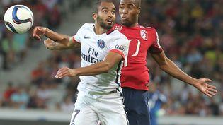 Le Parisien Lucas Moura à la lutte avec le Lillois Djibril Sidibe, lors du match entre le PSG et le Losc, le 7 août 2015. (FRANCOIS NASCIMBENI / AFP)