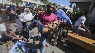 Un Palestinien porte un enfant blessé, après le bombardement d'une école de l'ONU à Rafah, dans le sud de la bande de gaza, le 3 août 2014. ( IBRAHEEM ABU MUSTAFA / REUTERS)