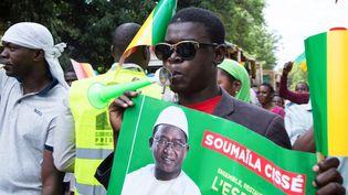 Un militanttient une affiche sur laquelle figure l'opposant malien Soumaïla Cissé, lors d'une marche de protestation contre les résultats de la présidentielle au Mali, le 1er septembre 2018, à Bamako. (ANNIE RISEMBERG / AFP)
