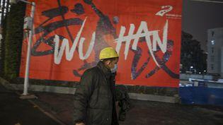 Un homme porte un masque dans une rue de Wuhan (Chine) le 26 janvier 2020 pendant l'épidémie de coronavirus. (HECTOR RETAMAL / AFP)