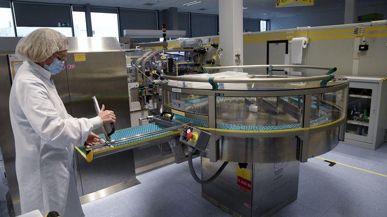 Une employée de la société britannique GSK sur une ligne de production d'adjuvants, le 3 décembre 2020, dans l'usine de Saint-Amand-les-Eaux (Nord). (FRANCOIS LO PRESTI / AFP)