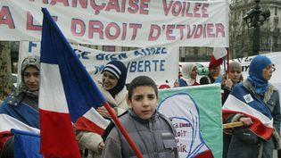 Des personnes manifestent le 14 février 2004 de la place de la République à Paris, pour protester contre le projet de loi interdisant le port ostensible de signes religieux (JEAN-LOUP GAUTREAU / AFP)