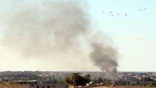 De la fumée au-dessus d'immeubles après des tirsde roquettes des forces armées du gouvernement libyen à Syrte (Libye), le 18 juillet 2016. (MAHMUD TURKIA / AFP)