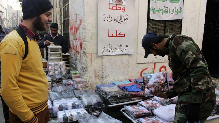 Stand de vêtements tenu par l'Armée syrienne libre à Alep (Syrie), le 21 novembre 2013. Accrochée au mur, une photod'Abdel Qader Saleh, tué trois jours plus tôt dans un raid aérien des forces de BacharAl-Assad. (MOLHEM BARAKAT / REUTERS)
