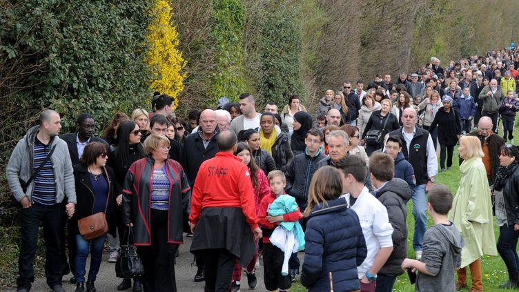 Des habitants et des parents d'élèves participent à la marche silencieuse en hommage aux victimes du directeur d'école accusé de viols, à Villefontaine (Isère). (JEAN-PIERRE CLATOT / AFP)