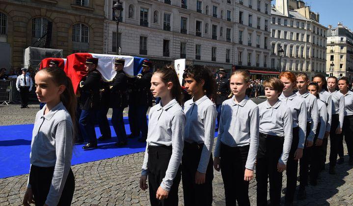 Rue Soufflot : des chanteurs de la Maîtrise populaire de l'Opéra Comique accompagnent les cerceuils.  (Blondet Eliot-POOL/SIPA)