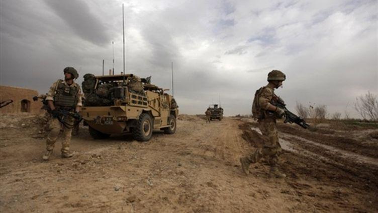 Soldats britanniques sur la route au nord-est de Marjah le 21 février 2010 (AFP. P.Baz)