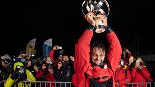 Le skipper français Yannick Betsaven brandit le coupe de la victoire du Vendée Globe 2020, aux Sables-d'Olonne (Vendée), le 28 janvier 2021. (LOIC VENANCE / AFP)