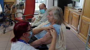 """Une résidente de l'Ehpad """"Les Oyats"""" de Gravelines, près de Dunkerque (Nord), est vaccinée contre le Covid-19, le 15 janvier 2021. (SYLVAIN LEFEVRE / HANS LUCAS)"""