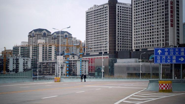 Des habitants de Wuhan, en Chine, portent un masque de protection contre le Covid-19, le 28 mars 2020. (ALY SONG / X01793 / REUTERS)