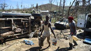 Un jeune homme porte des seaux d'eau à Jérémie, Haïti, le 9 octobre 2016. (HECTOR RETAMAL / AFP)