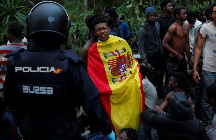 Un migrantrevêt le drapeau espagnol après avoir franchi la clôture entre le Maroc et l'enclave espagnole de Ceuta, le 17 février 2017. (REUTERS)