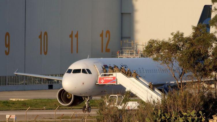 Les forces maltaises tentent d'entrer dans l'avion d'Afriqiyah Airways détourné par des pirates libyens, le 23 décembre 2016,sur le tarmac de l'aéroport de La Valette. (DOMENIC AQUILINA / AFP)