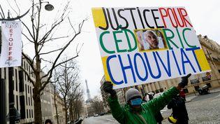 """Un manifestant tient une pancarte """"Justice pour Cédric Chouviat"""" durant une marche en hommage au chauffeur-livreur mort à la suite d'un contrôle de police, le 5 janvier 2020, à Paris. (SAMEER AL-DOUMY / AFP)"""