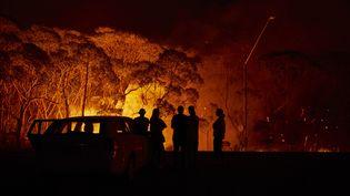 Des habitants observent la progression d'un feu de broussailles près du lac Tabourie (Nouvelle-Galles du Sud), samedi. (BRETT HEMMINGS / GETTY IMAGES ASIAPAC)