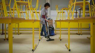 Une femme de ménage nettoie le sol d'une salle de classe du collège Notre-Dame Jean-Paul II de Ploemeur (Morbihan), qui continue d'accueillirles élèves dont les parents sont indispensables à la gestion de l'épidémie, le 16 mars 2020. (MANON CAVERIBERE / HANS LUCAS / AFP)