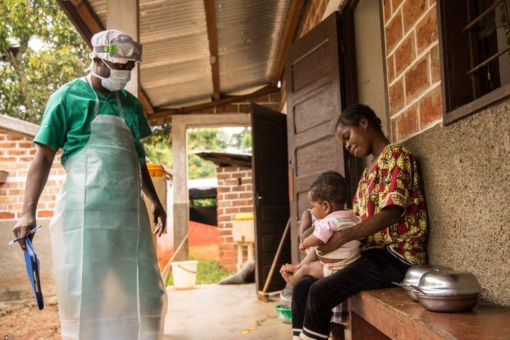 Une femme et son enfant, infectés par la variole du singe, attendent pour recevoir un traitementdans un centre de Médecins sans Frontières (MSF) près de Lobaya, dans le sud-ouest de la Centrafrique, le 18 octobre 2018. (CHARLES BOUESSEL / AFP)