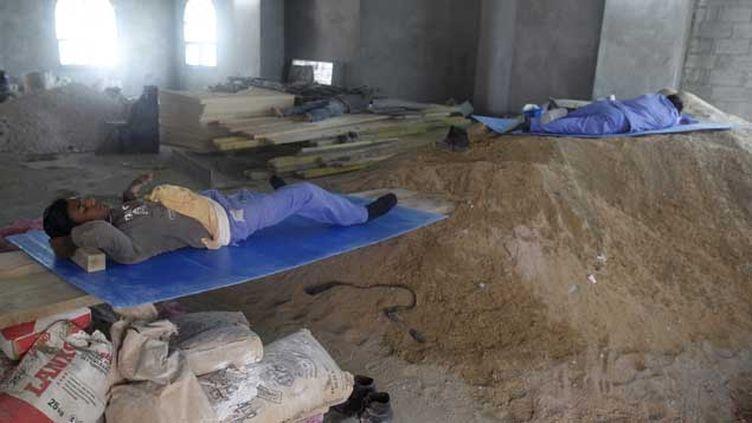 (Deux ouvriers immigrés sur un chantier à Doha se reposent pendant leur pause déjeuner. © Reuters)