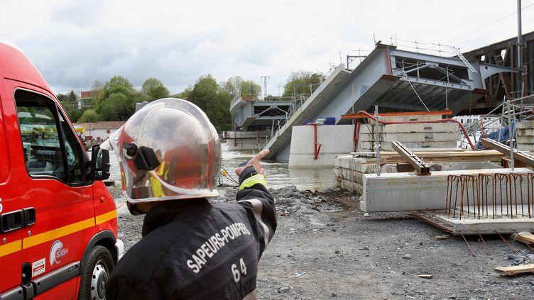 Un pompier devant le pont métallique qui s'est effondré à Bayonne, le 5 mai 2012. (CHOPIN JEAN DANIEL / MAXPPP)