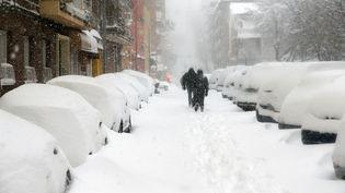 Des passants dans une rue de Madrid, en pleine tempête Filomena, le 9 janvier 2021. (SENHAN BOLELLI / ANADOLU AGENCY / AFP)