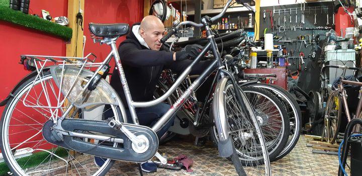 Abdel Benaissa, gérant dela boutiqueL'Eco Vélo, à Paris, répare une bicyclette, le 13 décembre 2019. (RAPHAEL GODET / FRANCEINFO)
