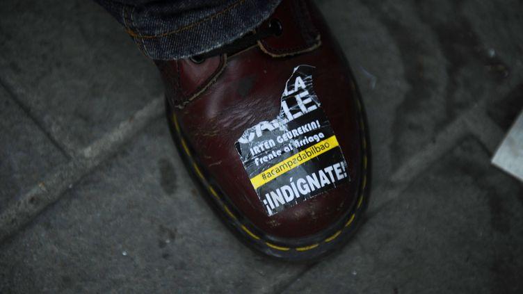 """Un homme porte un autocollant """"Indigne-toi !"""" lors d'une manifestation à Bilbao (Espagne), le 20 mai 2011. (VINCENT WEST / REUTERS)"""