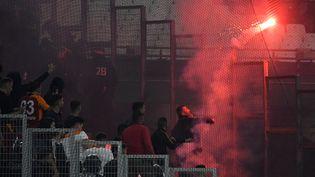 Un supporter de Galatasaray jette un fumigène dans les travées du stade Vélodrome, le 30 septembre 2021. (NICOLAS TUCAT / AFP)