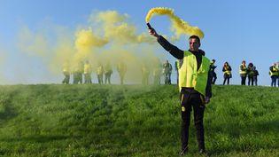 Un homme tient un fumigène jaune, à Bordeaux (Gironde),le 17 novembre 2018. (NICOLAS TUCAT / AFP)