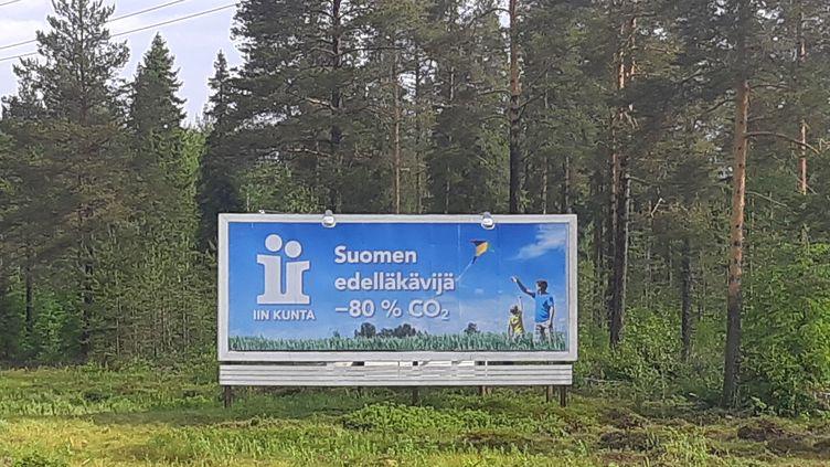 Le panneau d'entrée à Ii avec ses ambitions en matière d'émission de gaz à effet de serre. (MARIE-PIERRE VEROT/ RADIO FRANCE)