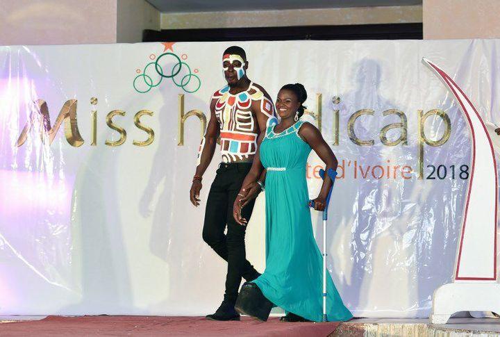 Accompagnée par un guide, une candidate malvoyante défile sur le podium lors du premier concours Miss handicap Côte d'Ivoire en mai 2018. (Photo AFP/Sia Kambou)