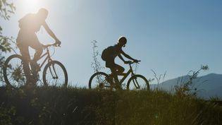 Deux touristes profitent du soleil pour se balader à vélo. (MAXPPP)
