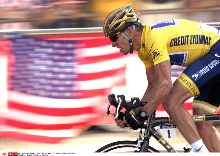 Lance Armstrong passe devant un drapeau américain, sur le parcours du Tour de France, le 25 juillet 2004 sur les Champs-Elysées, à Paris. (FRANCK PREVEL / AP / SIPA / AP)