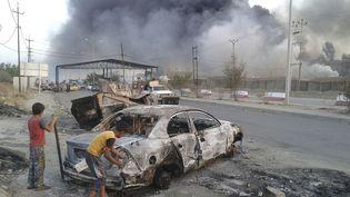 Des enfants assistent à des affrontements entre les forces de sécurité irakiennes et des jihadistesdu groupe l'Etat islamique en Irak et au Levant à Mossoul (Irak), le 10 juin 2014. (REUTERS)