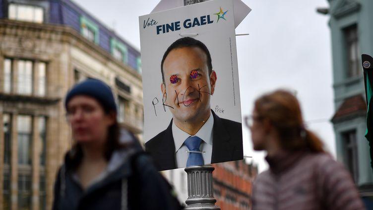 Des piétons passent devant une affiche électorale taguée représentant le Premier ministre irlandais Leo Varadkar, vendredi 7 février 2020 à Dublin. (BEN STANSALL / AFP)